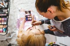 Retrato surrealista de la señora joven que hacen maquillaje con el espejo Imagen de archivo libre de regalías