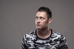 Retrato temperamental do homem atlético novo sério na camisa militar que olha afastado no copyspace imagem de stock royalty free