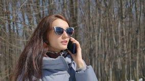 Retrato temprano de la primavera de la mujer joven que habla con alguien que usa su smartphone al aire libre en el parque en fond almacen de video
