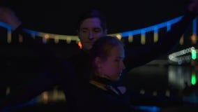Retrato tirado de dos artistas en los trajes negros que hacen girar el poi llevado en la noche almacen de metraje de vídeo