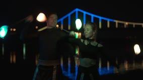 Retrato tirado de dos artistas hombre y mujer en los trajes negros que hacen girar el poi llevado almacen de video