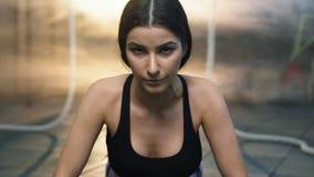 Retrato tirado de la mujer joven atractiva que empuja hacia arriba durante entrenamiento en el gimnasio metrajes