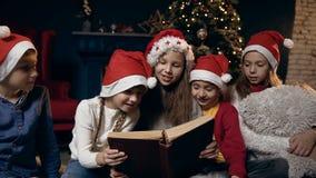 Retrato tirado de la sentada hermosa del libro de lectura de los niños cerca del árbol de navidad almacen de metraje de vídeo
