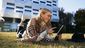 Retrato tirado de mensaje que mecanografía lindo de la mujer joven a los amigos en su tableta mientras que miente en la hierba almacen de video