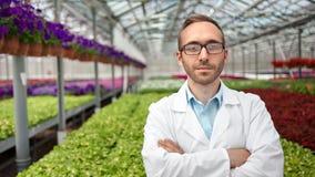 Retrato tirado medio del granjero de sexo masculino confiado sonriente de la ciencia que presenta en el invernadero que mira la c almacen de metraje de vídeo