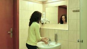 Retrato traseiro da vista de uma moça com mãos de lavagem da camisa amarela e do cabelo escuro na bacia no banheiro video estoque
