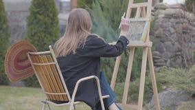 Retrato traseiro da vista do pintor da moça que senta-se na frente da armação de madeira que tira uma imagem e um fumo fêmea vídeos de arquivo