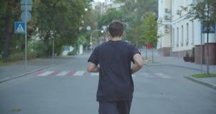 Retrato trasero de la opinión del primer del basculador masculino deportivo caucásico adulto que camina abajo de la calle en la c almacen de metraje de vídeo