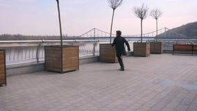 Retrato trasero de la opini?n del primer del hombre de negocios afroamericano atractivo joven que camina y que baila feliz en la  almacen de video