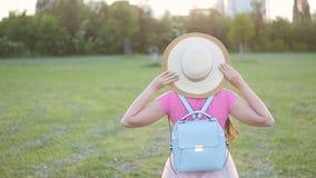Retrato trasero de la visión de la mujer joven en el parque La muchacha alegre atractiva goza del sol en parque almacen de metraje de vídeo