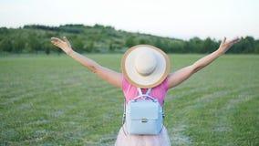 Retrato trasero de la visión de la mujer joven en el parque La muchacha alegre atractiva goza del sol en parque metrajes