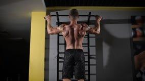 Retrato trasero de la visión de un hombre muscular que aprieta en el estudio del gimnasio almacen de metraje de vídeo