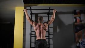 Retrato trasero de la visión de un hombre muscular que aprieta en el estudio del gimnasio almacen de video