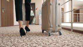 Retrato trasero de la visión de una mujer de negocios en traje chaqueta en los tacones altos que camina con su maleta a lo largo  almacen de video