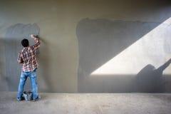 Retrato trasero de los trabajadores que enyesan la textura del cemento fotografía de archivo