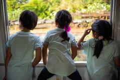 Retrato trasero de tres hermanas que miran hacia fuera la ventana del tra fotografía de archivo