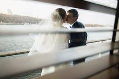 Retrato a través de la persiana de besar a la pareja nuevamente casada feliz Imágenes de archivo libres de regalías