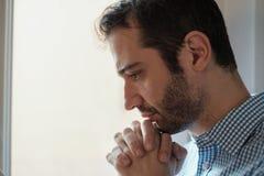 Retrato triste del hombre que mira fuera de la ventana Imagen de archivo libre de regalías