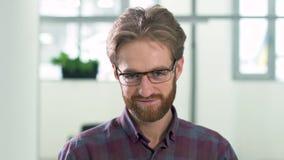 Retrato um indivíduo farpado smilling com vidros em uma posição diária da camisa de manta no centro do escritório na entrada na vídeos de arquivo