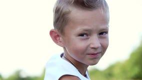 Retrato, um menino de sete, em um t-shirt branco Férias em família alegres, felizes Fora, no verão, perto da floresta video estoque
