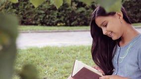 Retrato Uma menina bonita com cabelo longo lê um livro que senta-se sob uma árvore e sonhos sobre algo agradável video estoque
