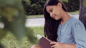 Retrato Uma menina bonita com cabelo longo lê um livro que senta-se sob uma árvore e sonhos sobre algo sorriso agradável filme