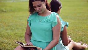 Retrato Uma menina bonita e uma menina bonito estão sentando na grama de volta à leitura traseira um livro e estão usando uma tab filme