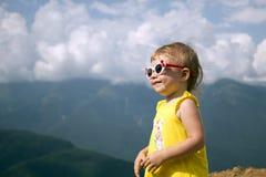 Retrato un pequeño niño en el fondo de las gafas de sol de montañas Foto de archivo libre de regalías
