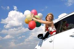 Retrato una muchacha en el coche con los globos coloridos Fotos de archivo