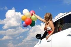 Retrato una muchacha en el coche con los globos coloridos Imagenes de archivo
