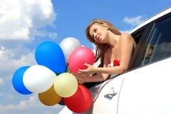 Retrato una muchacha en el coche con los globos coloridos Foto de archivo libre de regalías