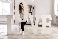 Retrato una mujer joven cerca de las letras grandes del amor de la palabra Fotografía de archivo libre de regalías