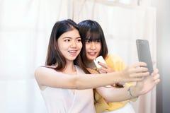 Retrato una sonrisa adolescente asiática hermosa de la mujer, feliz, diversión y selfie con smartphone Imágenes de archivo libres de regalías