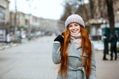 Retrato urbano da mulher positiva do gengibre com o cabelo longo que veste w fotos de stock