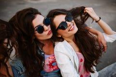 Retrato urbano de la forma de vida elegante brillante de dos muchachas bonitas de los mejores amigos que presentan en el rosa bri Imágenes de archivo libres de regalías