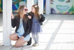 Retrato urbano de la madre feliz con la pequeña hija Imagen de archivo libre de regalías