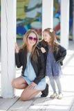 Retrato urbano de la madre feliz con la pequeña hija Foto de archivo libre de regalías