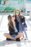Retrato urbano de la madre feliz con la pequeña hija Fotos de archivo