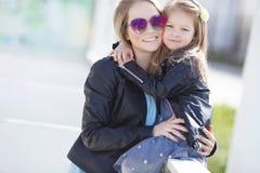 Retrato urbano de la madre feliz con la pequeña hija Imagen de archivo