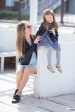 Retrato urbano de la madre feliz con la pequeña hija Imagenes de archivo