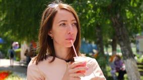 Retrato urbano del batido de leche de consumición de la mujer caucásica atractiva joven almacen de metraje de vídeo