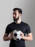 Retrato vago intenso del jugador de fútbol que sostiene la bola que mira lejos Fotografía de archivo