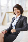 Retrato vertical de la empresaria asiática sonriente, sentándose imagen de archivo libre de regalías