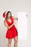 Retrato vertical de la muchacha de la Navidad con la placa en el fondo blanco Imagen de archivo
