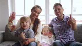 Retrato video da família feliz com as duas crianças que acenam as mãos filme