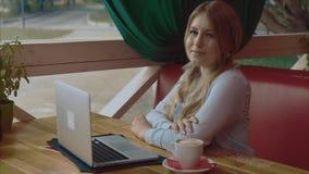 Retrato video de la empresaria joven que trabaja en el ordenador portátil en café almacen de video