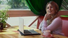 Retrato video de la mujer de negocios joven que sonríe con el ordenador portátil en café almacen de metraje de vídeo