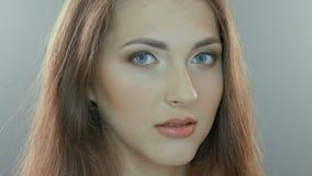 Retrato video de uma jovem mulher, isolado no cinza vídeos de arquivo