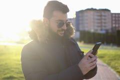 Retratos barbudos del hombre del invierno con el teléfono fotos de archivo