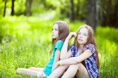 Retratos de la niña dos que se sienta en el parque Imágenes de archivo libres de regalías
